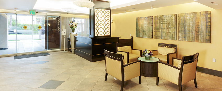 tiled lobby with yellow walls and 3 paintings on the wall