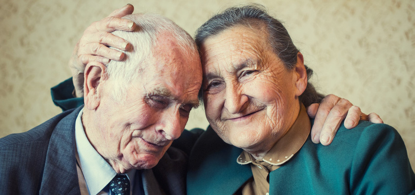elderly couple hugging each other with textured wallpaper in the background