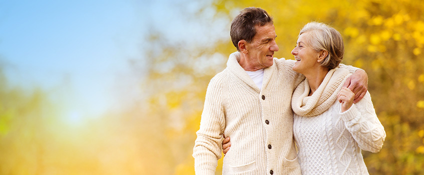 couple in wool sweaters smiling with each other outside during fall