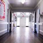 long hallway with wood floors and activity calendar posted on the wall