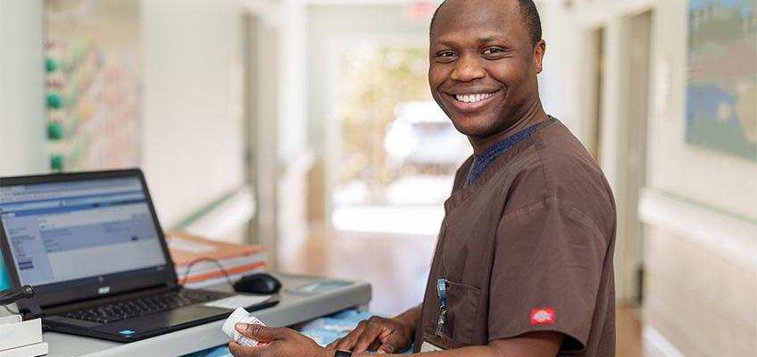 A smiling gentleman at a computer