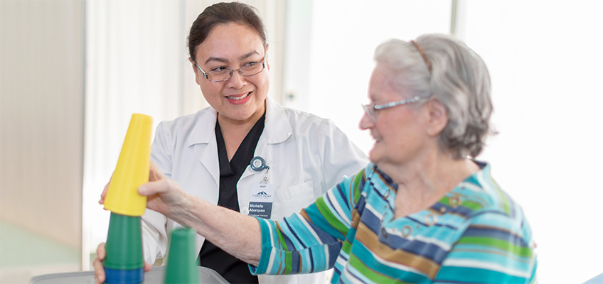 An elderly woman and a nurse practicing memory