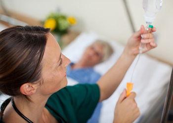 nurse administering an IV to a patient