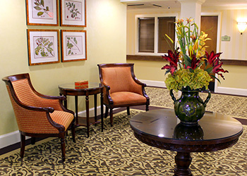 lovely sitting area with upholstered chairs, artwork on the walls and fresh flowers