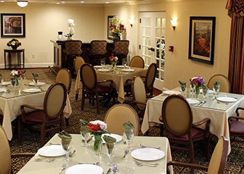 elegantly appointed dining room with tables set and flowers on each table