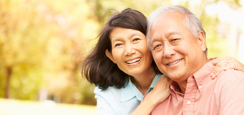 asian couple smiling and hugging in a park