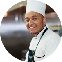 chef smiling in kitchen with fridge in the background