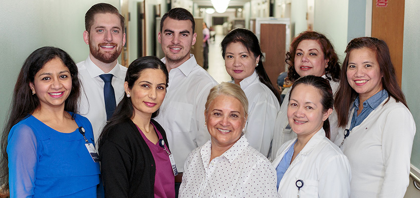large staff photo with everyone smiling and doctors coats