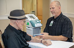 A staff member performing rehabilitative recovery care to a resident