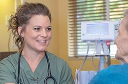 Nurse smiling at a resident as she checks vitals