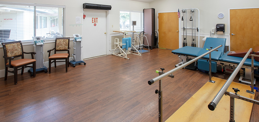 Rehabilitation gym with nicely organized equipment and clean hardwood floors
