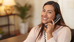 A Primrose staff member on the phone with a welcoming smile on her face.