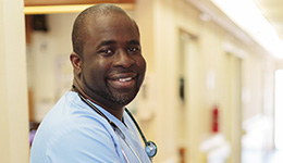 A staff member smiling with a stethoscope around his neck.