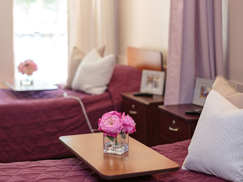 Double occupancy resident room with nicely made beds and flowers on a tray