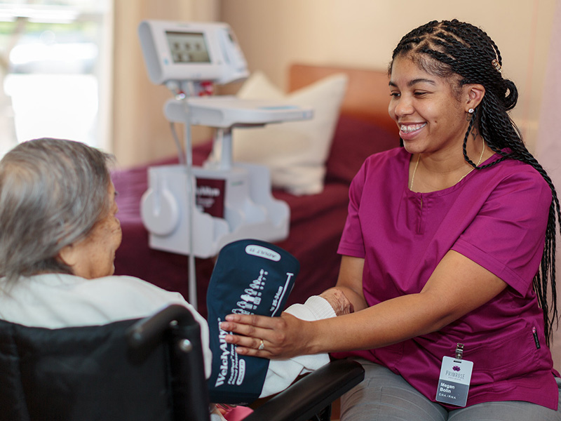 A staff member smiling at a resident at bedside checking vitals.