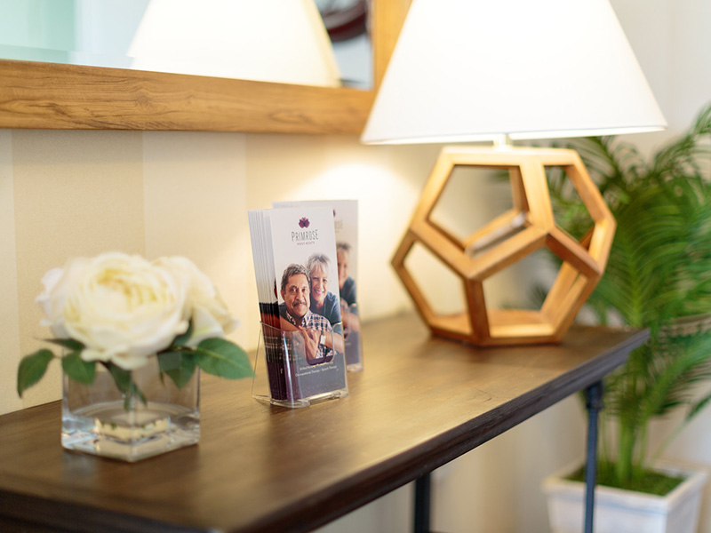 An end table with a rustic lamp lit showing the brochures and a vase filled with lush roses in bloom.