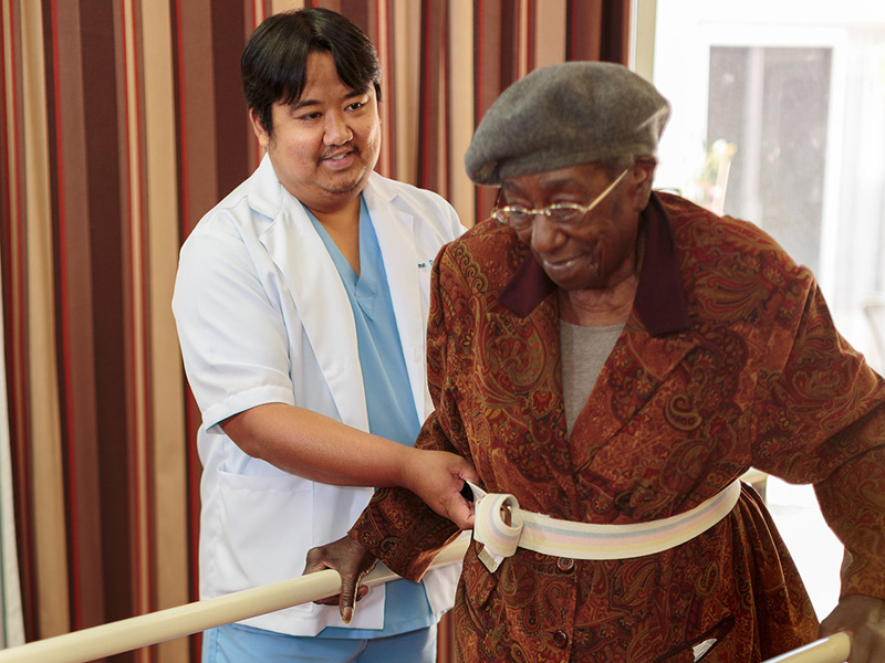 Rehabilitation staff assisting a resident with walking safely using the parallel bars.