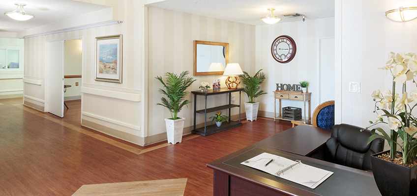 The front lobby of Primrose with indoor plants and a welcoming desk awaiting a new face.