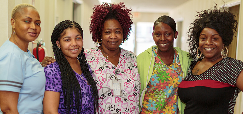 Primrose staff members standing together arm in arm in the hallway of the facility with large welcoming smiles on their faces.
