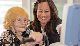 Resident working with rehabilitation staff on therapy exercises