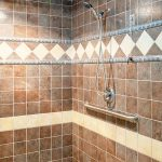 Beautifully tiled shower with rail and removable shower head