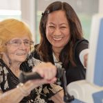 Rehabilitation staff member happily assisting a resident through her therapy exercises