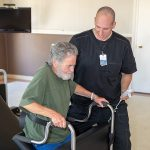 A rehabilitation staff member assisting a resident to his feet