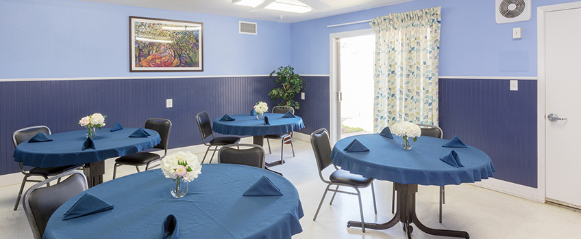 Nicely lit resident dining area with table covers and cloth napkins at each seating area and lush flowers in the center of each table