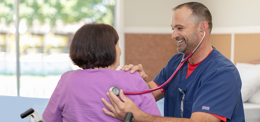 A nurse taking the vitals of a resident with a smile on his face