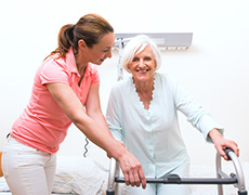 nurse assisting resident using a walker