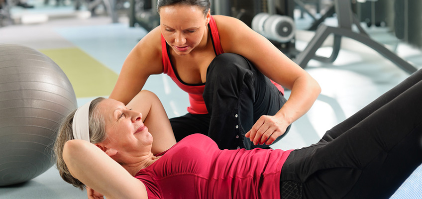 Therapist and patient working in the gym on core exercises