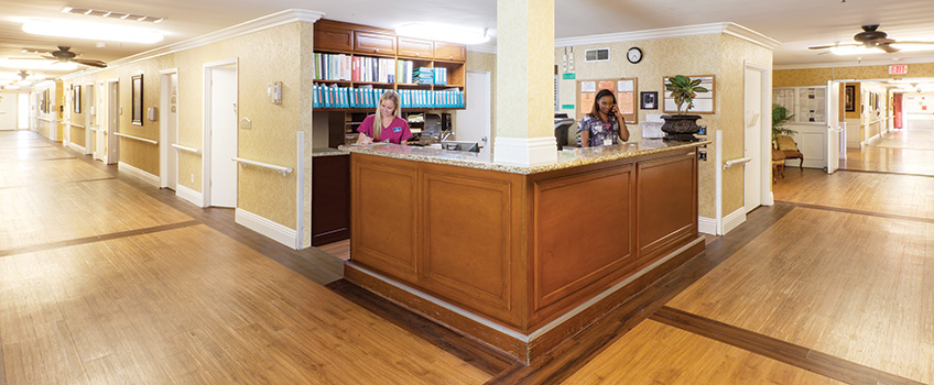 front desk with lot of files on the shelves and clean wooden hallways