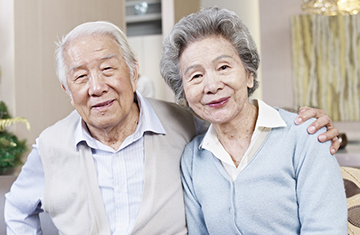 elderly couple seated with his arm around her shoulder