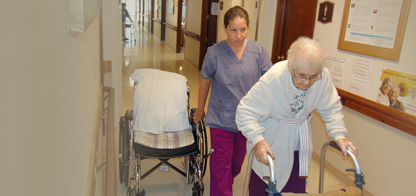 Nurse walking with a resident with a wheelchair handy in case she needs to take a break