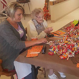 Resident assisting a staff member with filling bags with candy for Halloween