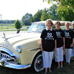 4 women standing beside an old car with shirts on that say '50 years of caring'