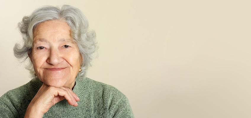 smiling elderly woman wearing a green sweater