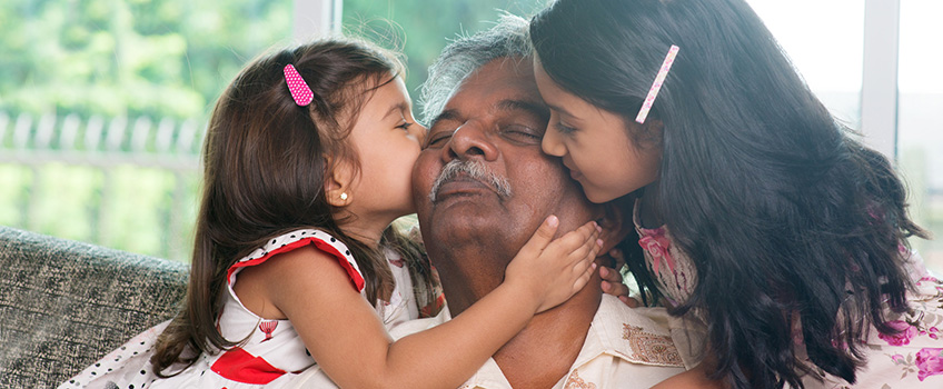 A grandpa getting a kiss on each cheek from his granddaughters