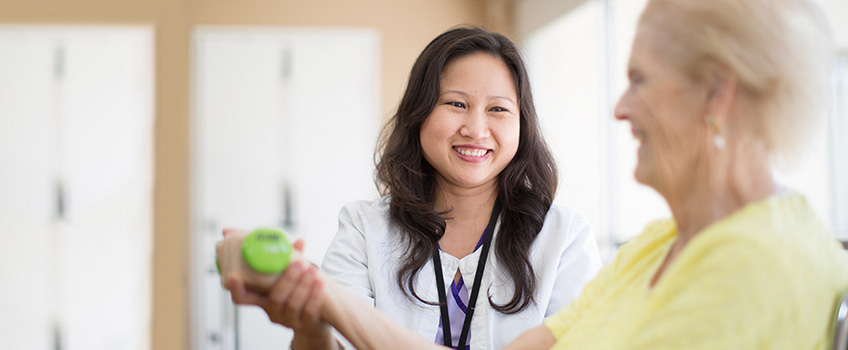 female asian doctor and older woman doing physical therapy