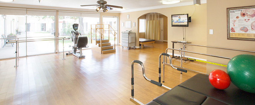 rehabilitation room with a big windowed wall and various equipment