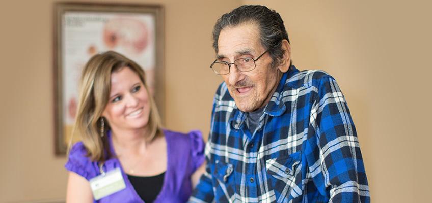 older man walking and a woman behind helping him smiling