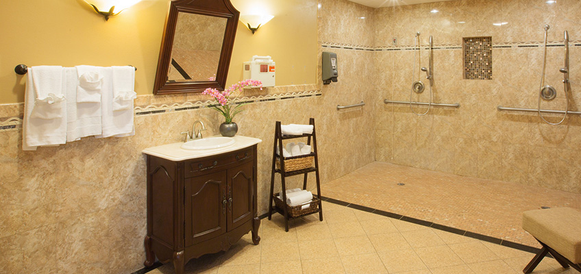 large shower room with two shower heads, sink and mirror