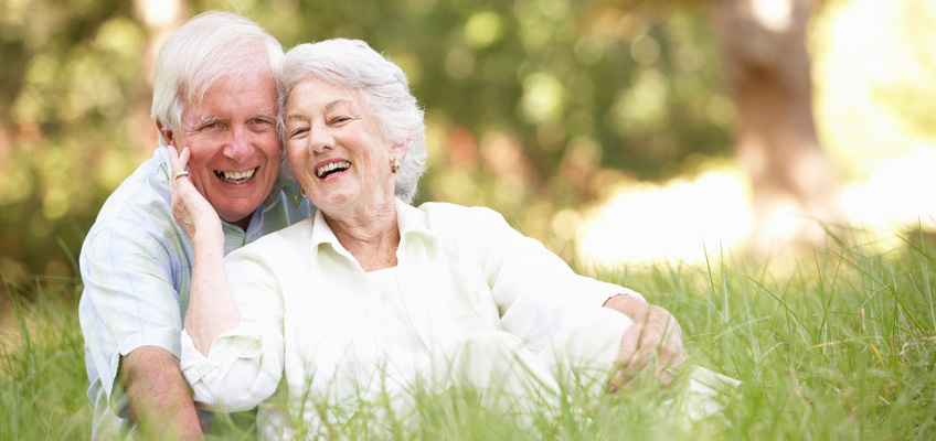 elderly couple smiling sitting in the grass outside