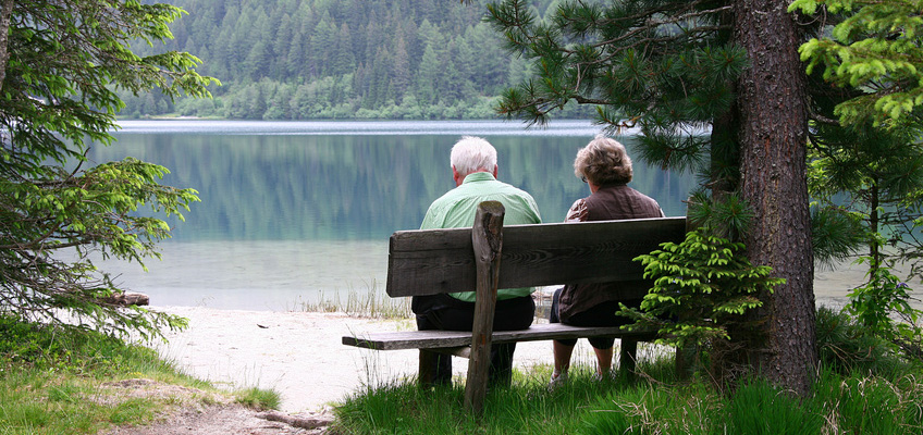 elderly couple sitting on a bench by a lake in the woods