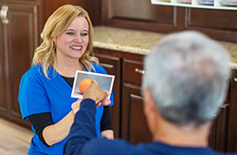 Therapist showing a picture of an orange to a resident
