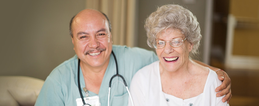 Smiling nurse and resident, the nurse has his arm around the resident's shoulder