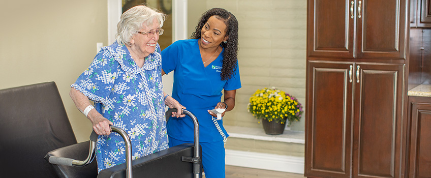 A smiling resident using a walker and being assisted by a nursing staff member