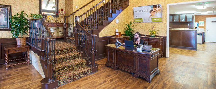 The reception desk at Highland Palms with dark hardwood floors, a wood and iron staircase and the receptionist desk made out of dark wood as well.