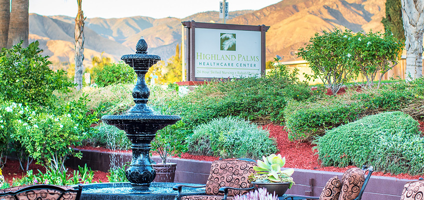 Highland Palms exterior sign located in front of a 3-tired fountain with mountains in the background