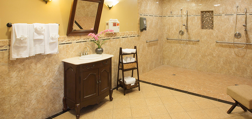 Handicapped accessible bathroom with double shower heads and tiles floor and walls